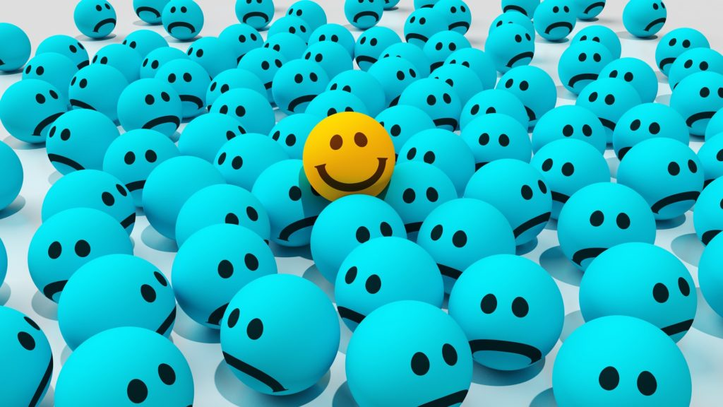 Blue and sad balls and one yellow happy ball to illustrate that a characteristic of a good project manager is a positive attitude